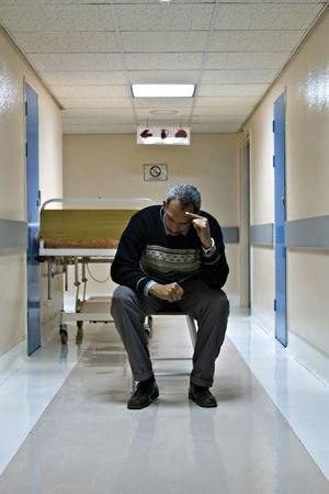 disrupt: mid age man waiting on the hospital hallway for his wife after surgery, healthcare series