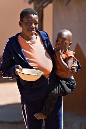 preocupacion: Rostro de la pobreza en el tercer mundo, la madre con ni�o en el duro sol del desierto de Kalahari, las cuestiones sociales serie