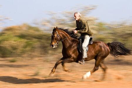 Senior man riding the horse in the bush, panning shot. photo