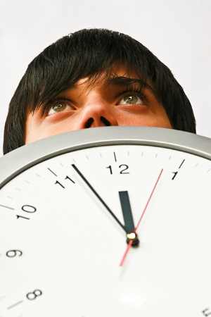 Young man behind a clock, isolated, passing time Stock Photo - 2112492