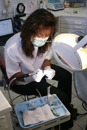 Dentist with rubber gloves polishing one porcelain tooth Stock Photo - 2112477