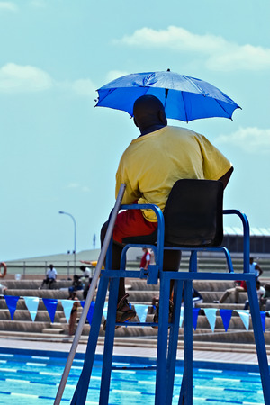 Official referee at a swimming competition, with umbrella, sitting on a tall chair. photo