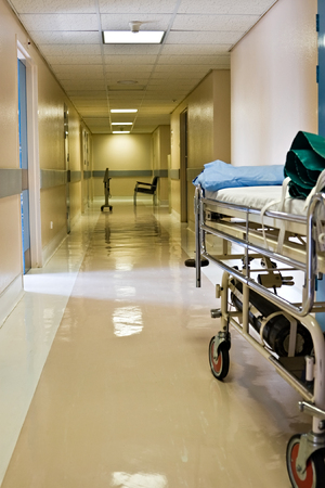 Empty hospital corridor, waiting chairs and bed Stock Photo