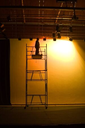 backstage: Man on scaffolding fixing the stage lights, preparing for the show