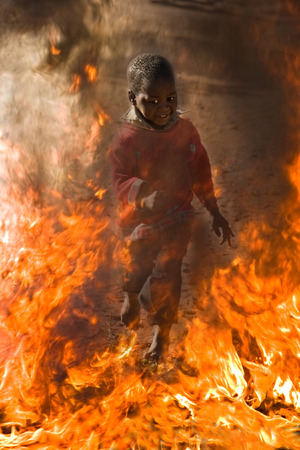 burn out: African American child surrounded by fire, running, escape, social issues series Stock Photo