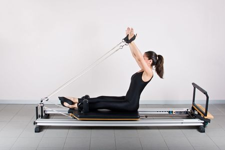 germanic: Arm reach extension position. Pilates gymnastics is a Germanic evolution of yoga, used by athletes to improve flexibility and body fitness and by chiropractors for patient recovery. Stock Photo