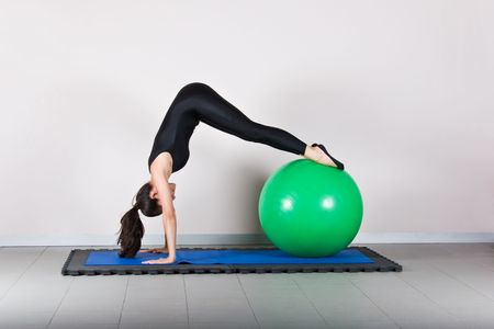 Downstretch with ball position. Pilates gymnastics is a Germanic evolution of yoga, used by athletes to improve flexibility and body fitness and by chiropractors for patient recovery. Stock Photo