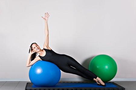germanic: Side bend  with ball position. Pilates gymnastics is a Germanic evolution of yoga, used by athletes to improve flexibility and body fitness and by chiropractors for patient recovery. Stock Photo