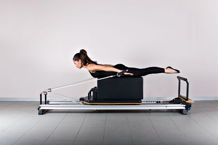 midlife: Spine twist and arms exercise. Pilates gymnastics is a Germanic evolution of yoga, used by athletes to improve flexibility and body fitness and by chiropractors for patient recovery.