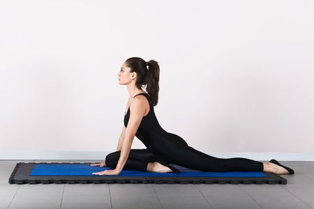germanic: pigeon position, soft focus. Pilates gymnastics is a Germanic evolution of yoga, used by athletes to improve flexibility and body fitness and by chiropractors for patient recovery. Stock Photo