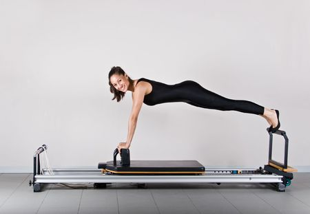 Reformer front support position. Pilates gymnastics is a Germanic evolution of yoga, used by athletes to improve flexibility and body fitness and by chiropractors for patient recovery.