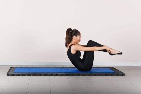 germanic: Rolling position. Pilates gymnastics is a Germanic evolution of yoga, used by athletes to improve flexibility and body fitness and by chiropractors for patient recovery. Stock Photo