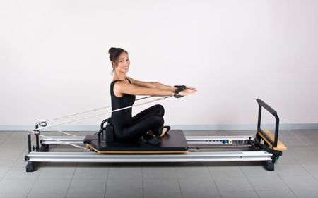 germanic: Arm stretch exercise. Pilates gymnastics is a Germanic evolution of yoga, used by athletes to improve flexibility and body fitness and by chiropractors for patient recovery.