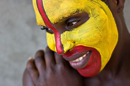 african warriors: Young African girl, tribal painted face in yellow and red