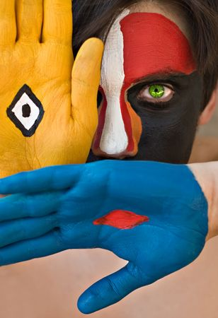 rhomb: Young man with colorful painted face, conceptual