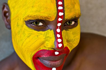african warriors: Young African girl, tribal painted face in yellow and red, green eyes