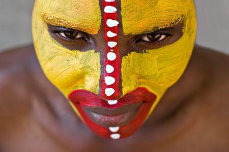 若いアフリカの女の子、部族の黄色と赤の顔を描いた
