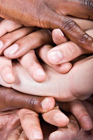 fingers on top: Background pile of hands, Caucasian, African American, Hispanic race. Stock Photo