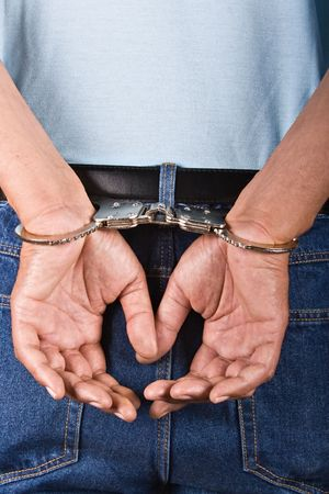 con man: Man handcuffed hands at the back, use it in security concepts Stock Photo