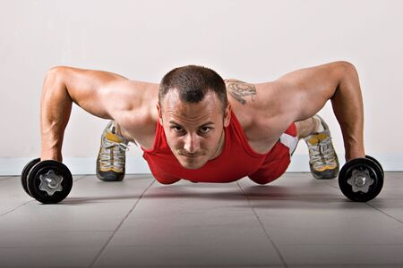 cardiovascular workout: Push up with dumbbells, classic endurance exercise for biceps Stock Photo