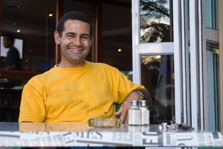 jovial: Happy man mixed race in a restaurant waiting for his coffee at the table Stock Photo