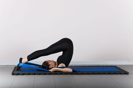 recovery position: Rollover with support  position. Pilates gymnastics is a Germanic evolution of yoga, used by athletes to improve flexibility and body fitness and by chiropractors for patient recovery. Stock Photo