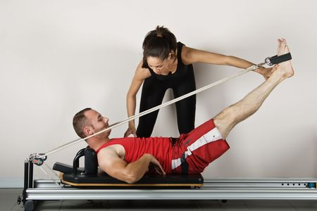 The reformer position with cords, student and trainer. Pilates gymnastics is a Germanic evolution of yoga, used by athletes to improve flexibility and body fitness and by chiropractors for patient recovery. Stock Photo