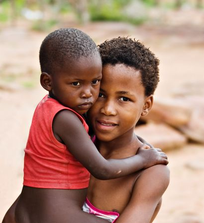 нищета: African children brother and sister, social issues, poverty, village near Kalahari desert
