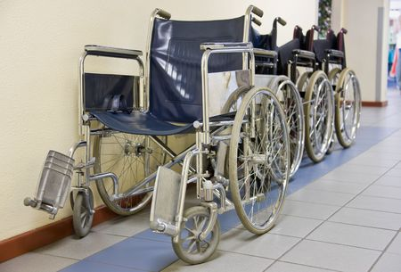 health facility: Wheelchairs parked on the side of a hospital hallway.