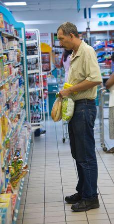 vend: old Hispanic man shopping in a supermarket, shelves displays