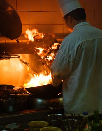 Chinese chef cooking on special stir fry stove, high flames, is shot on high ISO
