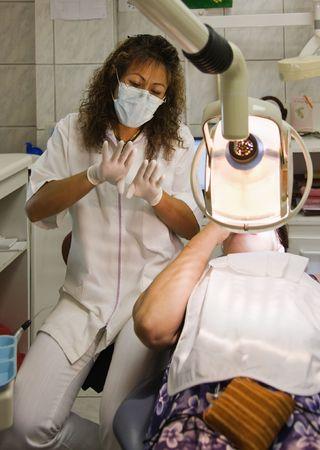 uniform curls: Hispanic dentist, explaining to the patient the procedure Stock Photo