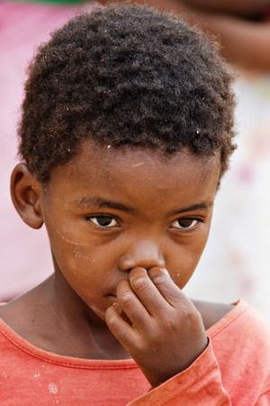 nose picking: African children picking his nose, social issues and poverty series,