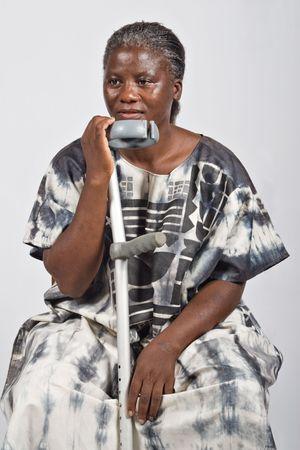 discapacidad: inv�lido de edad mujer africana con una muleta, el pelo blanco en la vestimenta tradicional, natural, sin maquillaje Foto de archivo