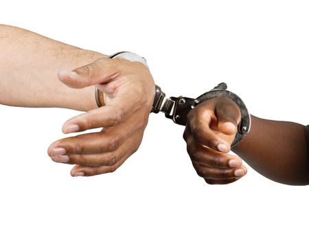 handcuffed Hispanic man hands and African woman isolated on white background photo