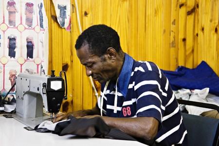 industria textil: �frica hombre de coser en una peque�a sastrer�a, m�quinas de coser industriales, la peque�a industria de �frica Foto de archivo