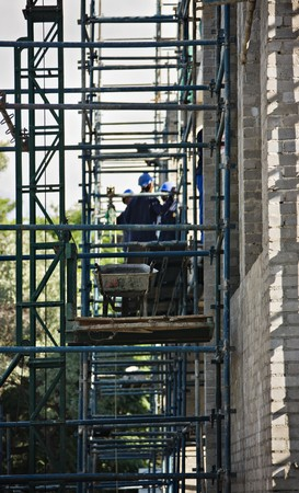 climbed: African American construction workers climbed on scaffolding,