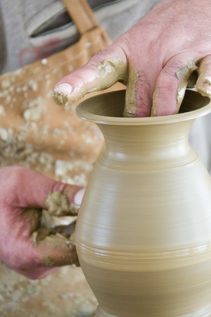 Man demonstrating how to create a ceramic pot photo
