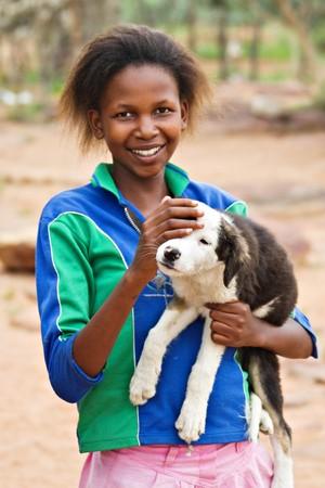 African girl with dog, picture taken in village near Kalahari Desert