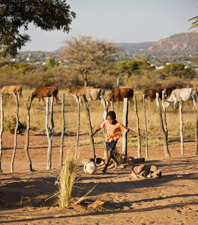 african village: African child playing football at the cattle post