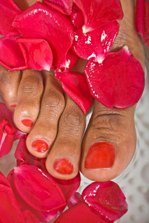 feet washing: woman washing her feet covered on rose petals, shoot  in a beauty parlor