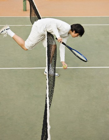 Young tennis player on the field picking the ball behind the net photo