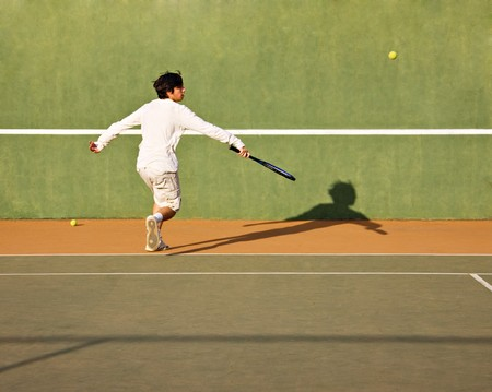Young tennis player on the field kicking the ball, warm look  photo