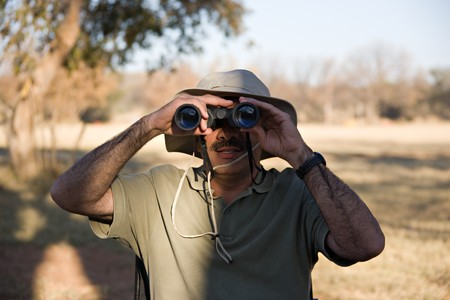 hairy arms: Man with binocular scouting in the bush after animals at sunset, location Botswana