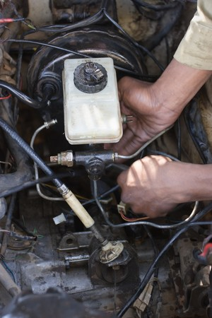 African American man fixing the brakes in an old car photo