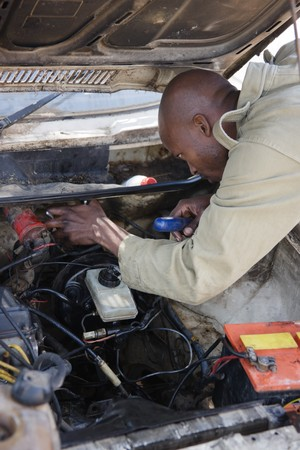 African American man fixing the brakes in an old car,  photo