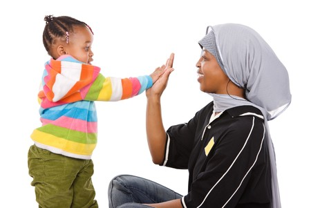 muslim baby girl: Muslim mother high five with her cute little African girl  Stock Photo