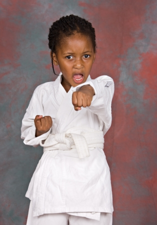 artes marciais: Small karate girl training , on colorful  background