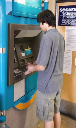 Young man withdrawing money from the ATM machine photo
