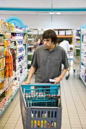 Young man walking with a trolley between the shelves photo